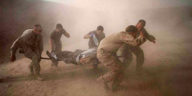 US Marines rush a colleague wounded in an IED strike in the volatile Helmand Province of southern Afghanistan on Tuesday, May 10, 2011.