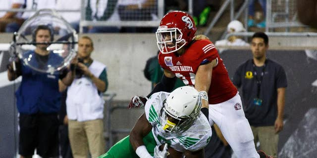 Oregon running back Byron Marshall makes a touchdown catch in the end zone during the second quarter of an NCAA college football game against South Dakota in Eugene, Ore., Saturday, Aug. 30, 2014. At right is South Dakota's Jacob Warner. (AP Photo/Ryan Kang)