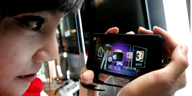July 7, 2011: A model looks at an LG Electronics Optimus 3D phone during a press conference in Seoul, South Korea.
