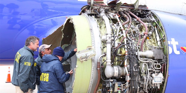 A National Transportation Safety Board investigator examines damage to the engine of the Southwest Airlines plane that made an emergency landing at Philadelphia International Airport.