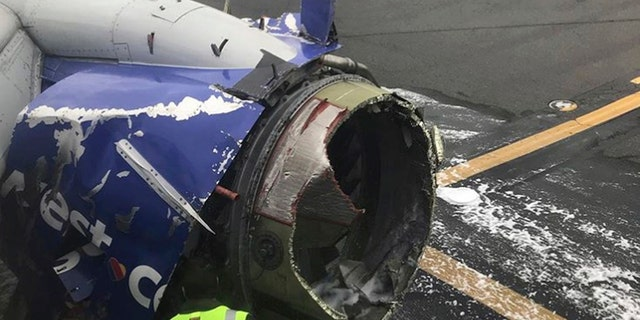 The engine on a Southwest Airlines plane is inspected as it sits on the runway at the Philadelphia International Airport after it made an emergency landing in Philadelphia, Tuesday, April 17, 2018.