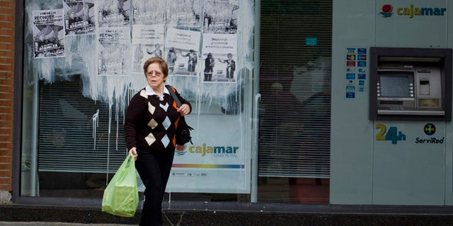 A woman leaves a bank plastered with protest posters in Madrid Monday May 21, 2012. (AP Photo/Paul White)