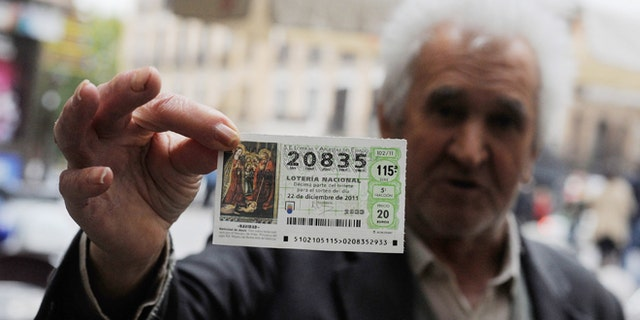 MADRID, SPAIN - NOVEMBER 09:  A man holds a Christmas 'El Gordo' lottery ticket he is hoping to sell on November 9, 2011 in Madrid, Spain. The current Eurozone debt crisis has left Spain with crippling economic problems. Mounting debts, record unemployment figures and the recent credit rating downgrade is leaving the country facing further economic stagnation. The people of Spain are preparing to go to the polls for a general election which will be held on November 20, 2011. (Photo by Denis Doyle/Getty Images)
