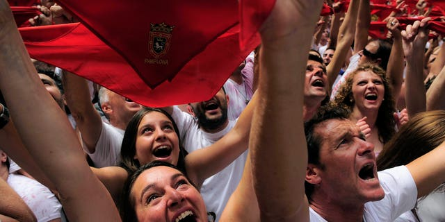 """Revelers hold up traditional red neckties as tens of thousands of people packed Pamplona's main square in Pamplona, northern Spain, Friday, July 6, 2012 to celebrate the start of Spain's most famous bull-running festival with the annual launch of the """"chupinazo"""" rocket. Perhaps best glorified by Ernest Hemingway's 1926 novel """"The Sun Also Rises,"""" the San Fermin festival is known around the world for the daily running of the bulls. (AP Photo/Alvaro Barrientos)"""