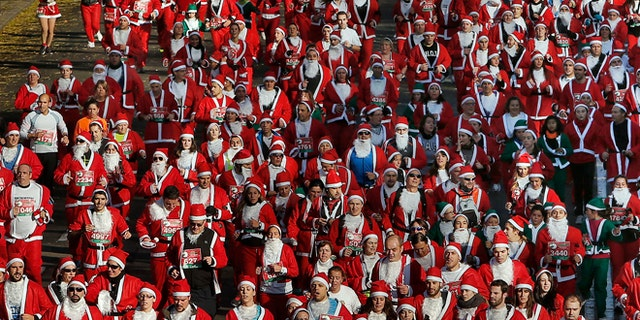 """Revelers dressed as Santa Claus run during a """"mini-marathon"""" in Madrid, Spain, Saturday, Dec. 14, 2013. Around 6,000 people dressed as Santa Claus and his elves have run a âmini-marathonâ through the streets of Madrid to promote festive cheer as the country tries to emerge from a two-year recession. While grown-ups dressed in red costumes with wispy white beards, children donned green elf outfits to run the 5.5 kilometer (3.4 miles) course through the city center. The race was organized Saturday by one of Spainâs leading department stores and it contributed 1 euro ($1.34) for each entrant to a charity that buys Christmas presents for deprived children around the world. (AP Photo/Andres Kudacki)"""