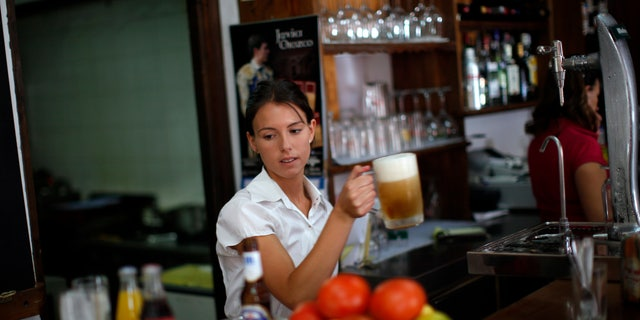 """July 24, 2014: Olalla Gomez, 22, a final-year student of English philology who is also on on the first day of her probation period before getting a contract as temporary waiter, holds a mug of beer in the """"Los Capeas"""" restaurant in downtown Ronda, near Malaga, southern Spain."""