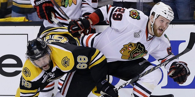 June 17, 2013: Boston Bruins right wing Jaromir Jagr (68), of the Czech Republic, ties up Chicago Blackhawks left wing Bryan Bickell (29) during the third period in Game 3 of the NHL hockey Stanley Cup Finals in Boston.