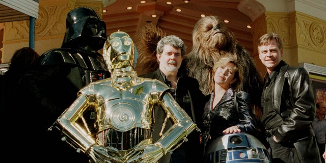 "Director and writer of ""Star Wars,"" George Lucas (C) poses with cast members Carrie Fisher and Mark Hamill along with characters ""Darth Vader"" (L) ""3CPO"" (in gold) ""R2D2"" (short robot) and ""Chewbacca"" (background) during the premiere of ""Star Wars Special Editon"" January 18, 1997 in Los Angeles."
