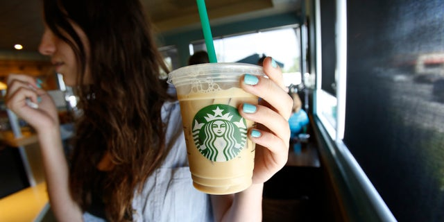 A patron holds an iced beverage at a Starbucks coffee store in Pasadena, California July 25, 2013. (REUTERS/Mario Anzuoni)