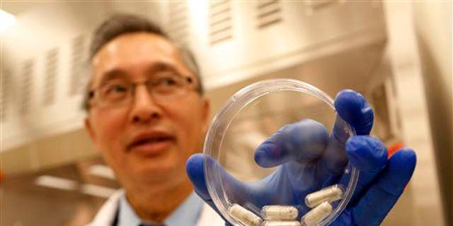 Dr. Thomas Louie, an infectious disease specialist, holds a container of stool pills in triple-coated gel capsules in his lab in Calgary, Alberta, Canada on Thursday, Sept. 26, 2013.