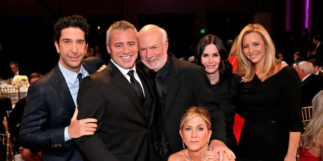 "Director James Burrows, standing center, poses with the cast of ""Friends,""  David Schwimmer, Matt LeBlanc, Jennifer Aniston, seated, Courteney Cox and Lisa Kudrow. (Chris Haston/NBC via AP)"