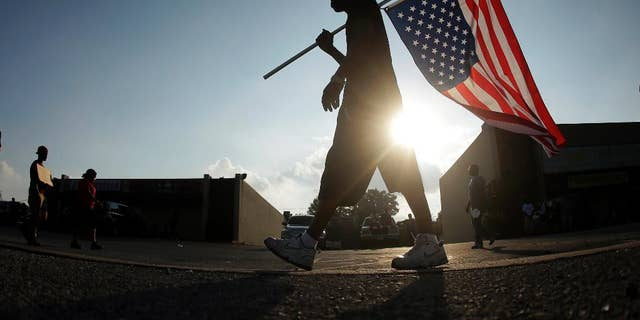 FILE - In this Aug. 18, 2014 file photo, Duane Merrells walks with an upside down American flag during a protest for Michael Brown in Ferguson, Mo. Ferguson officials were inundated with thousands of open-records requests from media outlets and the public following the shooting. In response, the St. Louis suburb sought payments of thousands of dollars before they would even begin to fulfill some of those requests, a decision defended by Ferguson's city attorney. The Missouri attorney general's office received several complaints from media outlets, including The Associated Press, that Ferguson was charging excessive fees.  (AP Photo/Charlie Riedel, File)