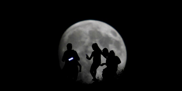 File photo - A group of hikers are seen silhouetted against the moon in Tijuana, Mexico, Aug. 27, 2015.
