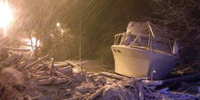 In this photo provided by Tom DeVito, a boat that washed ashore during Superstorm Sandy sits covered in snow on Hylan Blvd. in the Staten Island borough of New York as a nor'easter hits the city, Wednesday, Nov. 7, 2012.  (AP Photo/Tom DeVito)