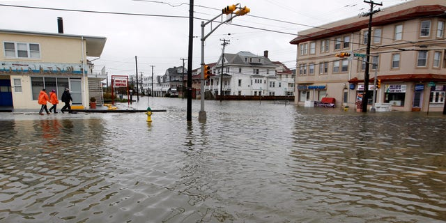 People walk along a flooded intersection of 8th Street and Atlantic Avenue, in Ocean City, N.J., Tuesday, Oct. 30, 2012, after the storm surge from Sandy flooded much of the town. Sandy, the storm that made landfall Monday, caused multiple fatalities, halted mass transit and cut power to more than 6 million homes and businesses. (AP Photo/Mel Evans)