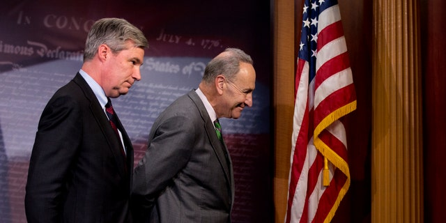 Sen. Charles Schumer and Sen. Sheldon Whitehouse leave a news conference on Capitol Hill, Wednesday, April 2, 2014.