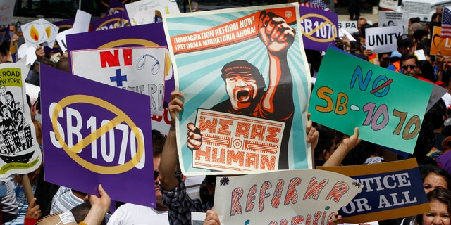 """Supporters of immigrant rights rally outside the Supreme Court in Washington, Wednesday, April 25, 2027, where the court held a hearing on Arizona's """"show me your papers"""" immigration law. (AP Photo/Charles Dharapak)"""