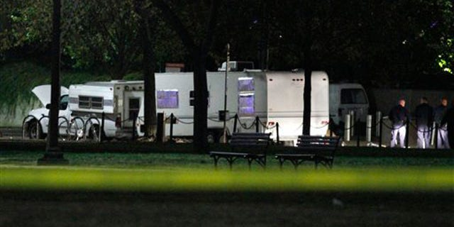 U.S. Park Police investigate a suspicious vehicle parked by the National Mall near the U.S. Capitol in Washington, on Wednesday, Nov. 3, 2010. U.S. Park Police say a man has been arrested after guns and ammunition were found inside a vehicle parked near the National Mall.