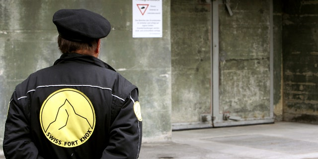 """A security guard stands in front of a gate of the Swiss Fort Knox bunker in the mountains near the Swiss Alpine resort of Saanen May 18, 2010. In the secret bunker, European researchers deposited a """"digital genome"""" that will provide the blueprint for future generations to read data stored using defunct technology."""