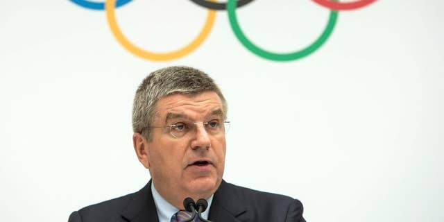 FILE - This is a Monday, July 7, 2014  file photo of International Olympic Committee, IOC, President Thomas Bach of Germany, as speaks during the announcement of the 2022 Olympic Winter Games Candidate Cities (Beijing 2022, Oslo 2022, Almaty 2022) after an executive board meeting, at the IOC headquarters in Lausanne, Switzerland. The IOC will not reopen the bidding process for the 2022 Winter Games after Oslo's withdrawal left just two cities in the race, IOC President Thomas Bach told The Associated Press on Thursday Oct. 2, 2014. (AP Photo/Keystone,Jean-Christophe Bott, File)