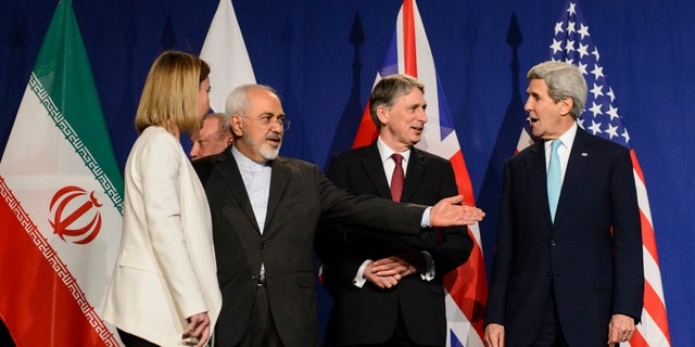 FILE - In this file photo taken Thursday, April 2, 2015, from left, EU High Representative for Foreign Affairs and Security Policy, Federica Mogherini, Iranian Foreign Minister, Mohammad Javad Zarif, British Foreign Secretary, Philip Hammond, and U.S. Secretary of State, John Kerry, line up for a press announcement after a new round of Nuclear Iran Talks in the Learning Center at the Swiss federal Institute of Technology (EPFL) in Lausanne, Switzerland.