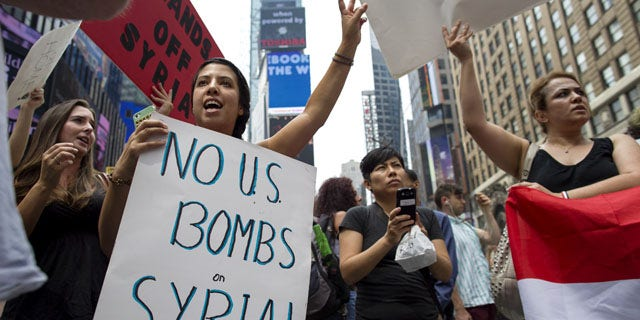 August 31, 2013: Rachel Lee Richards of New York. left, stands with opponents of a United States military strike against Syria as she and others protest at Times Square in New York