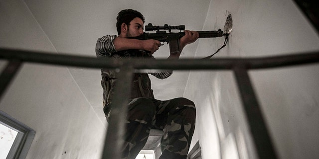 Oct. 30: A rebel sniper belonging to the Liwa Al-Fatah keeps an eye on an enemy position from a school building during skirmishes with the Syrian army in the nearby Bustan Al-Pasha front line in Aleppo.