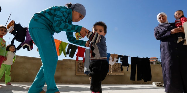 A Syrian refugee girl helps her brother, who the family suspects has polio, to walk as their mother watches in a mosque compound in Shebaa area, southern Lebanon October 28, 2018. (REUTERS/ Jamal Saidi)