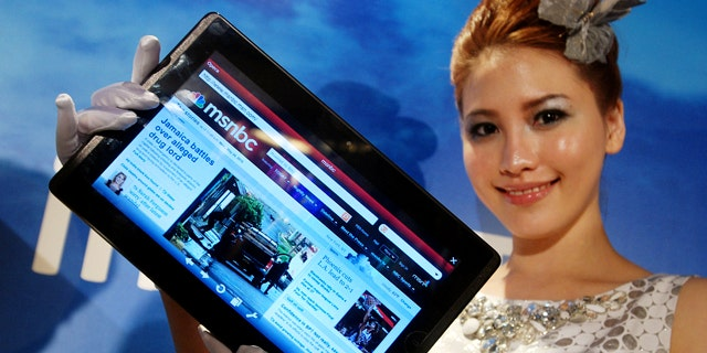 A model displays an AsusTek Eee Pad EP101TC tablet computer at an AsusTek new product media event on Monday, May 31, 2010, in Taipei, Taiwan. The 10-inch screen tablet, weighing 675 grams and measuring just 12.2 millimeters thick, is based on Windows and serves as a multimedia player, e-reader, compact PC and Internet device.