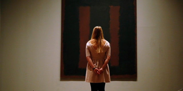 """A member of Tate staff poses with the restored Mark Rothko artwork """"Black on Maroon, 1958"""" at the Tate Modern in London May 13, 2014. The picture was vandalised in 2012 by Polish man Wlodzimierz Umaniec - known also as Vladimir Umanets - who wrote """"Vladimir Umanets '12 A potential piece of yellowism"""" on the canvas. He has since been given a jail sentence for the action. REUTERS/Luke MacGregor  (BRITAIN - Tags: CRIME LAW SOCIETY TPX IMAGES OF THE DAY) - RTR3OWAI"""