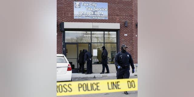 Detroit Police Officers check out the scene after a shooting injuring four people at a tax preparation business in Detroit, Friday, Feb. 28, 2014. Deputy Police Chief Rodney Johnson said a woman became upset when her tax refund wasn't ready Friday and started scuffling with the guard. Johnson said the man with her pulled a gun and started shooting. (AP Photo/Detroit Free Press, Jarrad Henderson)  DETROIT NEWS OUT; NO SALES; MANDATORY CREDIT