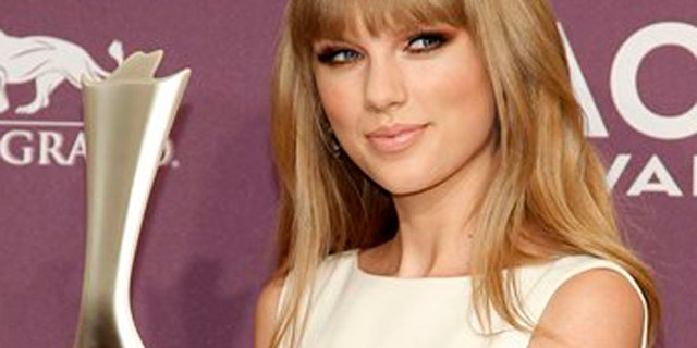 April 1, 2012: Taylor Swift poses backstage with the award for entertainer of the year at the 47th Annual Academy of Country Music Awards.