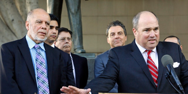 Nov. 21, 2014: Plaintiffs' attorney John Manly, right, with co-counsel Luis Carrillo, left, talks to reporters outside Los Angeles Superior Court