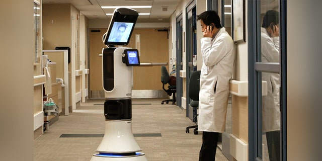 Dr. Alan Shatzel, medical director of the Mercy Telehealth Network, is displayed on the monitor RP-VITA robot as he waits to confer with Dr. Alex Nee at Mercy San Juan Hospital in Carmichael, Calif. (AP Photo/Rich Pedroncelli)