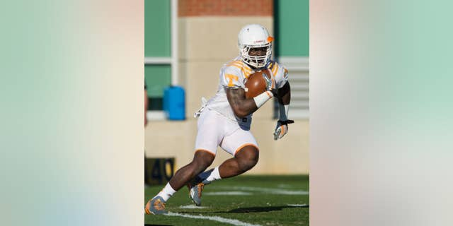 In this March 7, 2014 photo, University of Tennessee running back Marlin Lane participates in a drill during spring practice in Knoxville, Tenn. One year ago, Lane missed the end of spring practice for disciplinary reasons and had to work his way toward reinstatement. Now he's earning raves for continuing to practice and help lead a young offense despite dealing with a hand injury.(AP Photo/The Knoxville News Sentinel, Paul Efird)