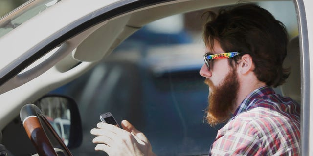 Feb. 26, 2013: A man uses his cell phone as he drives through traffic in Dallas.