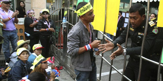 January 26, 2014: Anti-government protester talk to an election officer while gathering in front of a polling station in Patumwan district during a rally in Bangkok, Thailand. (AP Photo/Sakchai Lalit)