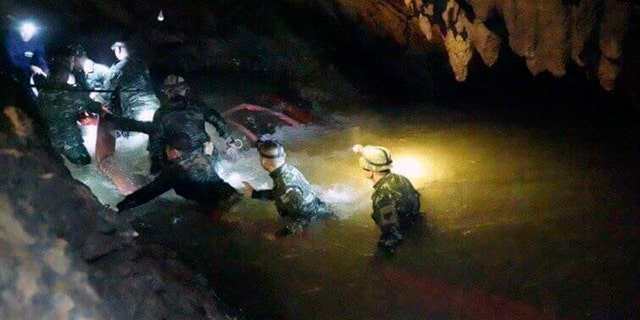 Thai rescue teams use headlamps to enter a pitch-black cave complex where 12 boys and their soccer coach went missing, in Mae Sai, Chiang Rai province, northern Thailand, Monday, July 2, 2018.