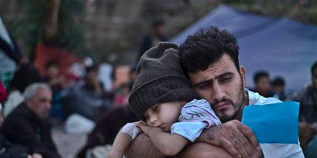 A Syrian refugee child sleeps on his father's arms while waiting at a resting point to board a bus, after arriving on a dinghy from the Turkish coast to the Greek island of Lesbos, Oct. 4 , 2015.