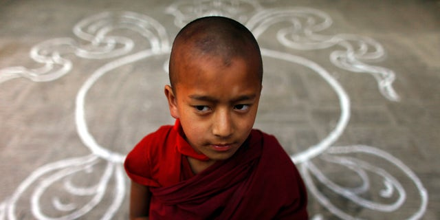 "A Tibetan monk stands at a Tibetan Monastery during the third day of ""Losar,"" or Tibetan New Year, at Baudhanath Stupa in Katmandu, Nepal, Friday, Feb. 24, 2012."