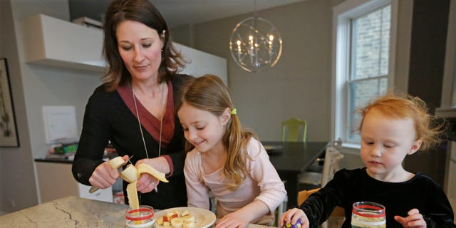 Kathy Burnett prepares a snack for her daughters Claudia, center, and Sabina right, after their gymnastics class Thursday, Jan. 29, 2015, in Chicago. (AP Photo/M. Spencer Green)