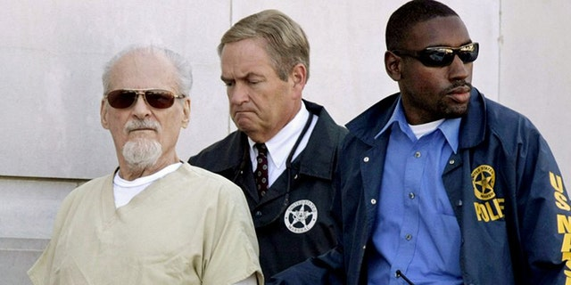 Tony Alamo is escorted to a waiting police car outside the federal courthouse in Texarkana, Ark. on July 23, 2009.