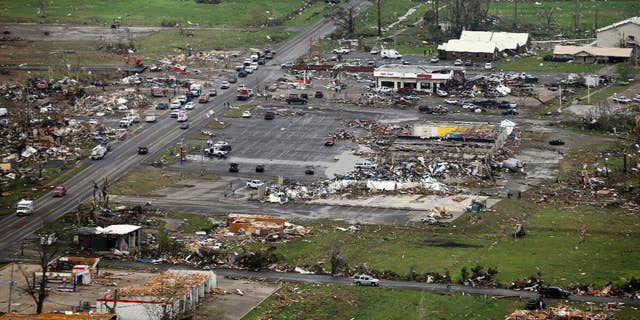 FILE - This Monday, April 28, 2014 aerial photo shows destroyed buildings and debris along U.S. Highway 64 in Vilonia, Ark. Vilonia was hit hard Sunday for the second time in three years. Four people were killed in a 2011 storm. Until this late April 2014 outbreak, the U.S. as a whole had by far the quietest start of the year for tornadoes. Longer trends show more tornado clusters recently. (AP Photo/Danny Johnston)