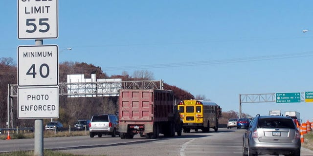 Nov. 12, 2013, file photo, of vehicles passing a highway sign along Interstate 380 in Cedar Rapids, Iowa, warning drivers that the 55-mph speed limit is enforced by speed cameras.