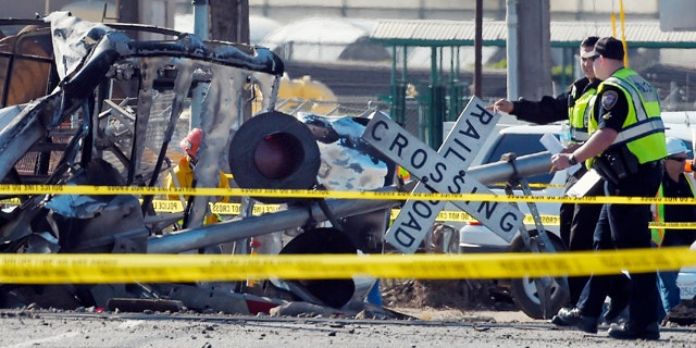 In this Tuesday, Feb. 24, 2015, photo Police officers stand near a Metrolink train that hit a truck, leftt, and then derailed at a railroad crossing in Oxnard, Calif. Three cars of the Metrolink train tumbled onto their sides, injuring dozens of people in the town 65 miles northwest of Los Angeles. Engineers have figured how to blunt the deadly force of a train smashing into a truck on the tracks. Yet few U.S. rail systems have adopted the technology, which is believed to have played a significant role in the remarkably low number of serious injuries from Tuesday's commuter rail crash. (AP Photo/Mark J. Terrill)