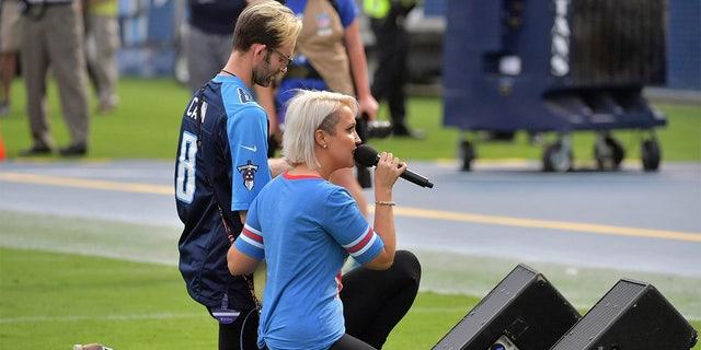 Recording artist Meghan Linsey kneels agter singing the national anthem