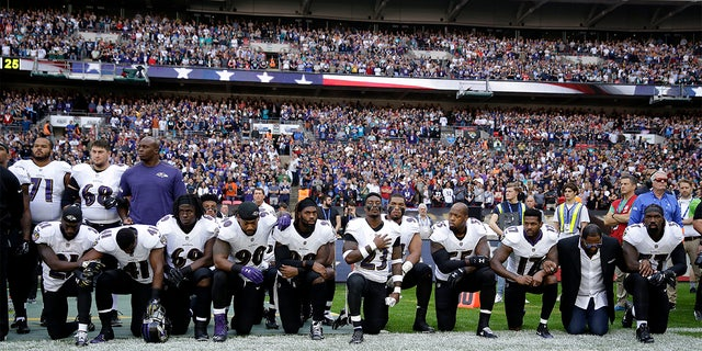 Jugadores de los Ravens de Baltimore, entre ellos el retirado linebacker Ray Lewis (segunda a la derecha) se arrodillan durante la interpretación del himno nacional previo al partido contra los Jaguars de Jacksonville en Londres, el domingo 24 de septiembre de 2017. (AP Foto/Matt Dunham)