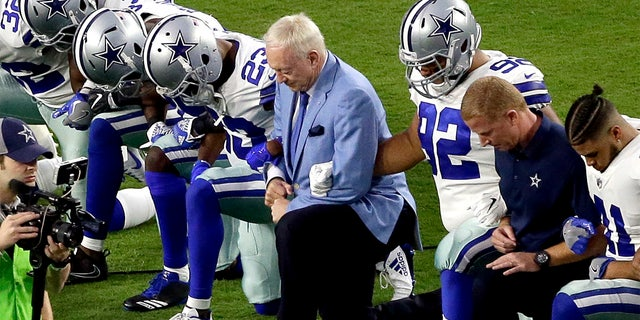 The Dallas Cowboys, led by owner Jerry Jones, center, take a knee prior to the national anthem