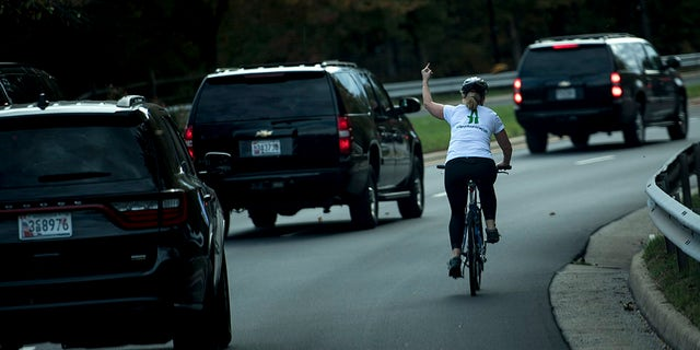 Juli Briskman gestures with her middle finger as a motorcade with US President Donald Trump departs Trump National Golf Course October 28, 2017 in Sterling, Virginia.