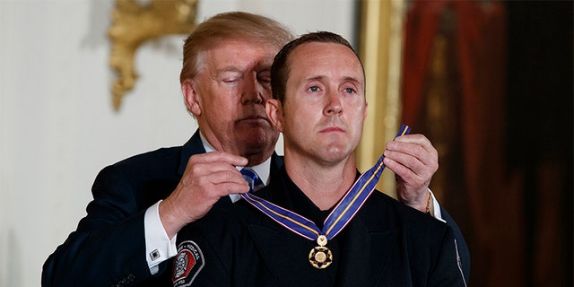 President Donald Trump awards public safety Medal of Valor to Engineer Stephen Gunn of Peoria (Ariz.) Fire-Medical Department during a ceremony in the East Room of the White House, Tuesday, Feb. 20, 2018, in Washington.